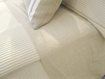 Beige bed sheets and bedcover in cotton